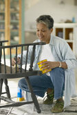 Senior woman painting chair — Stock Photo
