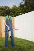 Hispanic woman painting fence — Stock Photo