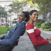 Freunden sitzend im park — Stockfoto