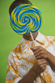 African boy holding big lollipop over face — Stock Photo