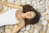 Hispanic woman in bathing suit lying on stones — Stock Photo