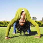 African woman doing back bend in grass — Stock Photo