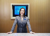 Businesswoman standing behind desk — Stock Photo