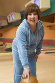 Woman holding bowling ball at bowling alley — Stock Photo