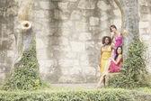 Three women next to ivy covered stone wall — Stock Photo