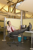 Businessman talking on phone with feet on desk — Stock Photo