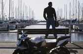 Young man standing on a pier bench — Stock Photo