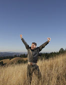 Elated man standing in field — Stock Photo