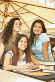Tre spansktalande kvinnor på café bord med skolböcker — Stockfoto