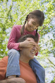 Hispanic father with daughter on shoulders — Stock Photo