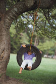 Young girl sitting in tire swing — Stock Photo