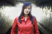 Portrait of a young woman looking at camera in front of tunnel — Stock Photo