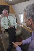 Businessmen talking onboard an airplane — 图库照片