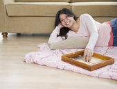 Young woman playing backgammon on living room floor — Stock Photo