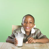 Portrait of African boy holding glass of milk — Stock Photo
