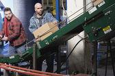 Two men operating conveyor belt — Stock Photo