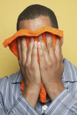 African man in pajamas holding washcloth to face — Stock Photo