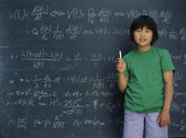 Portrait of girl holding chalk in front of chalkboard — Stock Photo