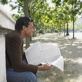 Man sitting with newspaper in urban park — Stock Photo
