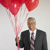 Portrait of Indian businessman holding balloons — Stock Photo