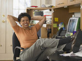 Businesswoman relaxing at her desk — Stock Photo