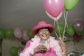 Portrait of senior adult woman in feather boa and hat with balloons — Stock Photo