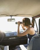 Hispanic woman looking through binoculars in car — Stock Photo