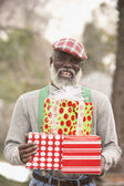 Senior African man holding presents — Stock Photo