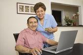 Senior Hispanic couple with credit card and laptop — Stock Photo