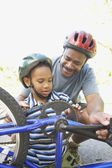 African American father helping son fix bicycle — Stock Photo