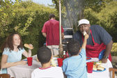 Family at a backyard barbecue — Stock Photo