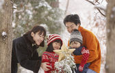 Family with star and snowy tree in forest — Stock Photo
