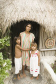 Mother posing with her children outside a straw hut — Stock Photo
