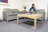Woman sitting in waiting room — Stock Photo
