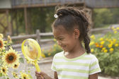 African girl looking at flower through magnifying glass — Stock Photo