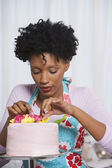 Young African woman putting flowers on cake — Φωτογραφία Αρχείου