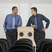Zwei geschäftsleute stützte sich auf podium — Stockfoto