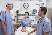 Asian boy in hospital bed with doctors talking — Stok fotoğraf
