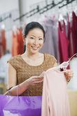 亚洲女人看在精品件衬衫的价格 — 图库照片