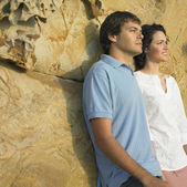 Young couple leaning against rock — Stock Photo