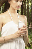 Woman holding glass of water in forest — Stock Photo