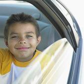 Portrait of boy looking out car window — 图库照片