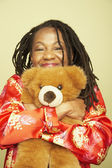 Middle-aged African woman hugging teddy bear — Stock Photo