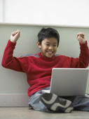 Young boy celebrating while using a laptop — Stock Photo