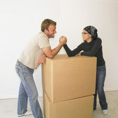 Couple arm wrestling on boxes in new house — Stock Photo