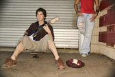 Young man playing guitar for money — Stock Photo
