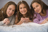 Hispanic sisters laying on bed with down feathers — Stock Photo