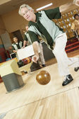 Man bowling at bowling alley — Stockfoto