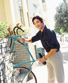 Young man carrying bicycle — Stock Photo