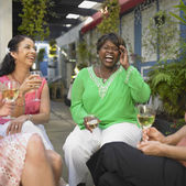 Young women relaxing together with wine — Stock Photo